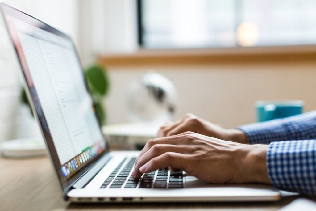 Notify billing companies - 10 things to remember when moving home - person typing on laptop