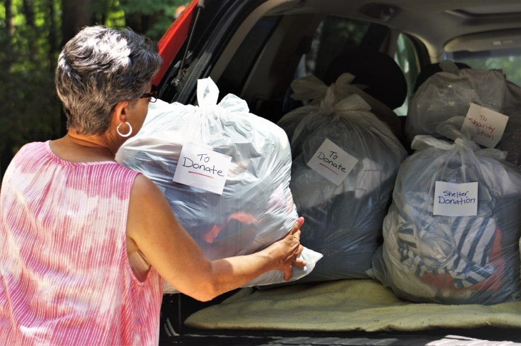 Woman putting bags of donations in car boot [Decluttering: How to help your loved one 'let go' of items - blog]