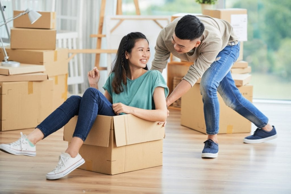Couple having fun in packing boxes [Decluttering: How to help your loved one 'let go' of items - blog]